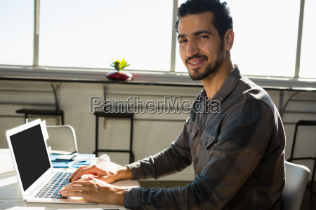 portrait of man using laptop at