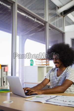 smiling young man using laptop at