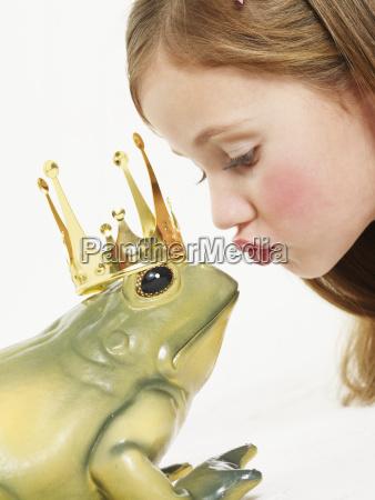 portrait of little girl kissing frog