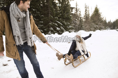 happy young couple with sledge in
