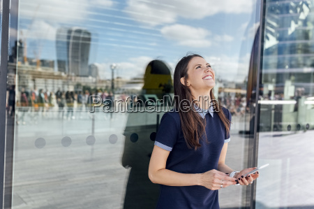 uk london happy woman with smartphone