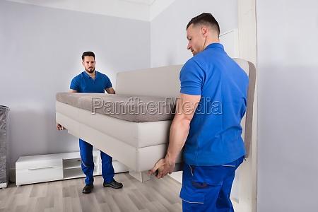 dois homens que prendem o sofa