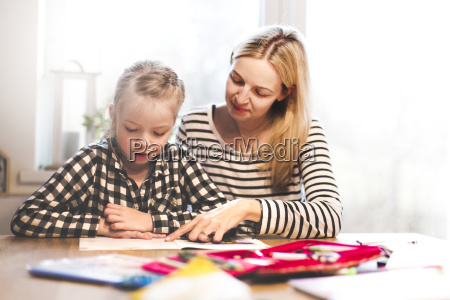 mother and daughter togehter doing schoolwork