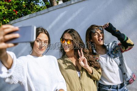 tres jovens sorridentes tirando selfie com