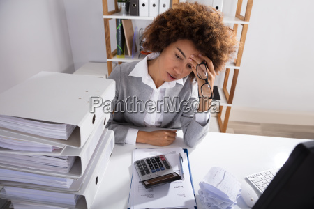 tired businesswoman sitting in office with