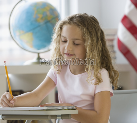 girl writing at school desk