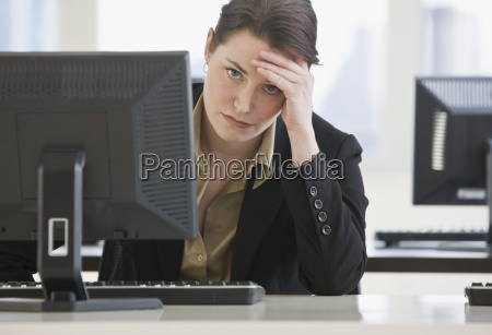 frustrated businesswoman leaning on desk