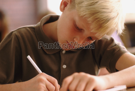 elementary school student writing at his
