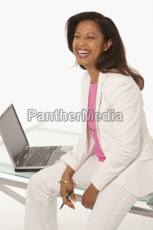 happy businesswoman sitting on desk