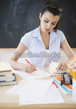 female teacher writing at desk