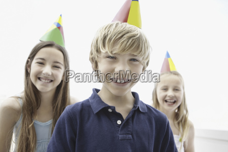 tres criancas que desgastam chapeus do