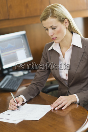 businesswoman writing at desk