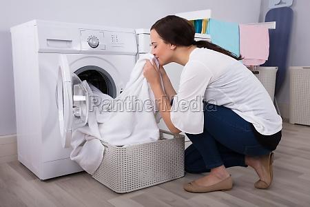 mulher cheirando pano apos lavar na
