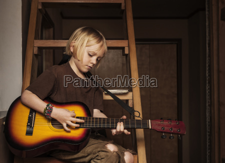 boy practicing guitar while sitting on