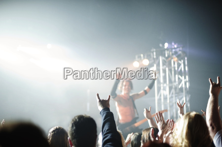 rock musician gesturing while performing at