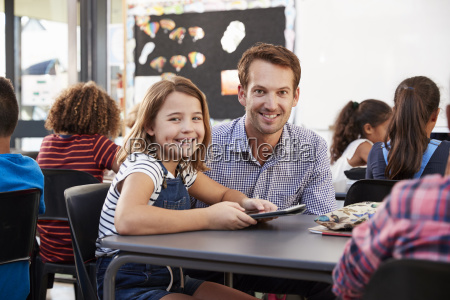 teacher and schoolgirl using tablet in