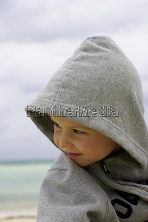 boy in hoodie on the beach