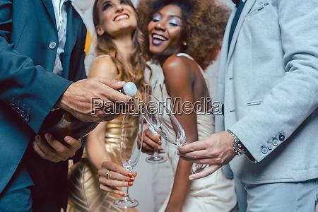 man opening champagne bottle on celebration