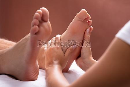 terapeuta dando massagem nos pes ao