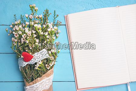 caderno aberto em branco e flores