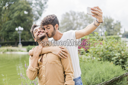 happy young gay couple taking selfie