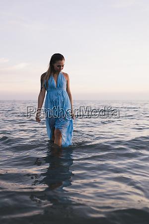 young woman wearing blue dress walking