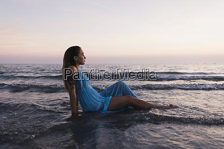 young tattooed woman wearing blue dress