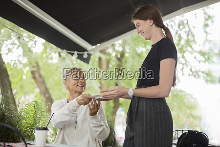 waitress handing over plate to smiling