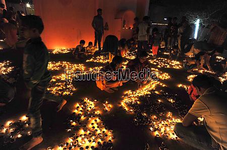 hindu devotees placing lit puja lamps