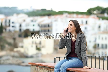mulher feliz falando ao telefone nas
