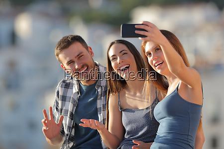 three happy friends taking selfies in