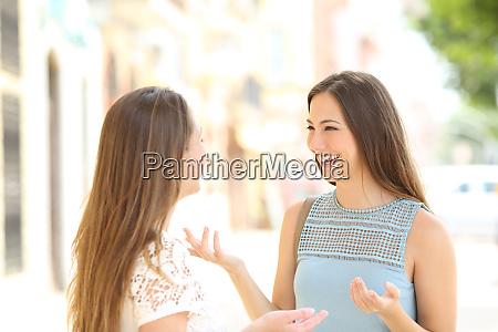 two happy casual friends talking in