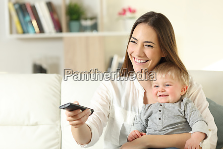 happy mother and baby watching tv