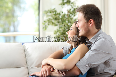 couple hugging sitting on couch at