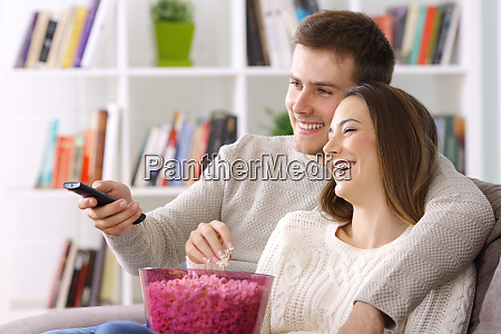 couple watching tv at home in