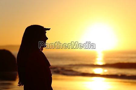 woman silhouette looking forward at sunset
