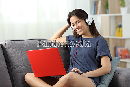 happy teen watching videos online at