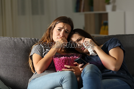 two sad friends crying watching tv
