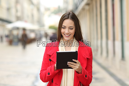 happy coman checking tablet content in