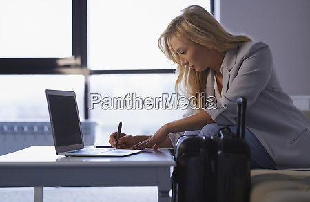 businesswoman working on laptop in airport