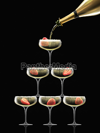 gold champagne bottle filling coupe glasses