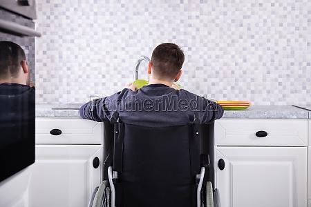 homem deficiente limpando pratos na cozinha