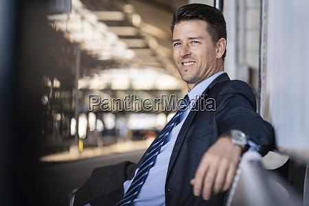 smiling businessman waiting on station platform