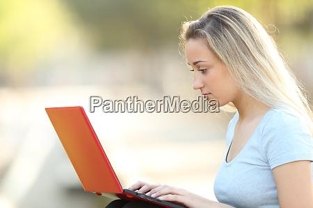 adolescente serio que usa um portatil