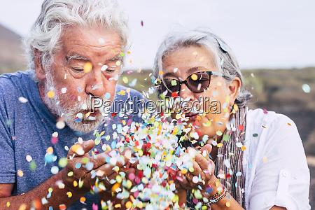 casal senior soprando confete ao ar