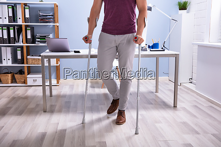 handicapped man walking with crutches