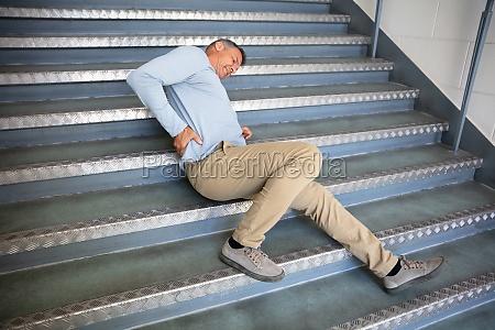 homem maduro deitado na escadaria