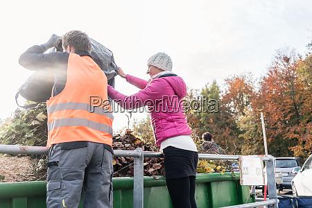 mulher e homem dando residuos verdes