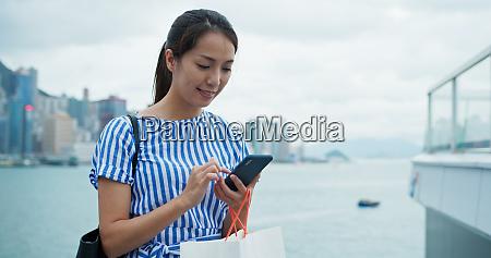 mulher usa celular na cidade