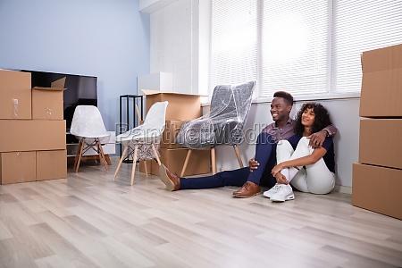couple sitting on floor inside their